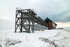 PCC BakkiSilicon - Zakończył się montaż konstrukcji taśmociągu. Na pierwszym planie widać skład surowego kwarcytu, w tle kryty magazyn do przejściowego przechowywania węgla.