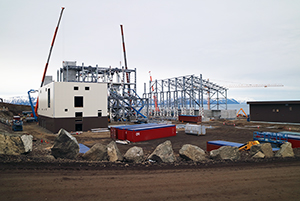 PCC BakkiSilicon - The photo shows the main electrical station with work in progress on the thermal insulation. Behind it you can see the furnace building, where steel construction elements are mounted using cranes. The yellow crane on the right is working on the steel structure of the part of the furnace building which will later house bunkers and storage facilities (large bins) for the produced silicon.