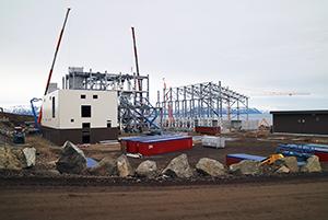 PCC BakkiSilicon - Auf diesem Bild ist vorne links das Hauptelektrohaus zu sehen, das gerade gedämmt wird. Dahinter befindet sich das Ofengebäude, bei dem die Installation des Stahlbaus mittels Kränen voranschreitet. Der gelbe Kran rechts arbeitet am Stahlbau des Teils des Ofenhauses, wo später Bunker und Lager für das fertige Silizium (in Form von großen Boxen) sein werden.