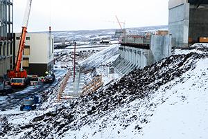 PCC BakkiSilicon - Auf diesem Bild sind Brückenstützen zu erkennen. Über die spätere Brücke werden im Betrieb acht Tagesspeicher (Silos) befüllt werden. Das Material aus den Silos wird dann unten auf der zweiten Terrasse (Produktion) entnommen und in das Ofengebäude (im Bild ganz links) befördert werden.