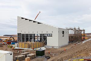 """PCC BakkiSilicon - Die Halle für die Produktverpackung ist fast fertig verkleidet. Rechts im Bild sind die Rahmen des """"Hairpin-Coolers"""" zu sehen, in denen später die Abgase der Öfen abgekühlt werden, bevor sie in das Filterhaus gelangen."""