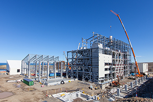 PCC BakkiSilicon - Construction of the steel structure for the product storage bay (front left) has nearly been completed and cladding work on the furnace building has started.