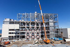 PCC BakkiSilicon - At the furnace building, the last steel construction girders are mounted, while the crane lifts the elements of the flue gas stacks into the building.