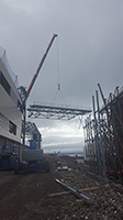 PCC BakkiSilicon - Einheben der ersten Rohrbrücke zwischen Ofengebäude und Haarnadelkühler. Über diese Brücke wird das Abgas den Kühlern und Filtern zugeführt.