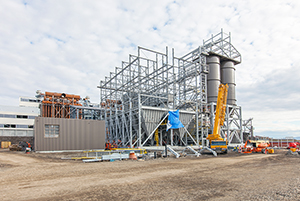 PCC BakkiSilicon - The construction of the off-gas cleaning facilities continues. The hairipin cooler, for cooling down the off-gas, is at the back left in brown. Steelwork for the filter station to collect dust from the off-gas is in the middle front. Silos, used for storage of the filtered dust, are at the front left.