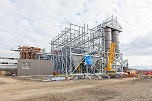PCC BakkiSilicon - Postępy na budowie instalacji spalin. Wymiennik płaszczowo-rurowy do chłodzenia spalin (brązowa konstrukcja w tle po lewej). Konstrukcja stalowa filtrowni do odpylania spalin (z przodu w środku). Zbiorniki pyłu do składowania pyłów (z przodu po prawej).